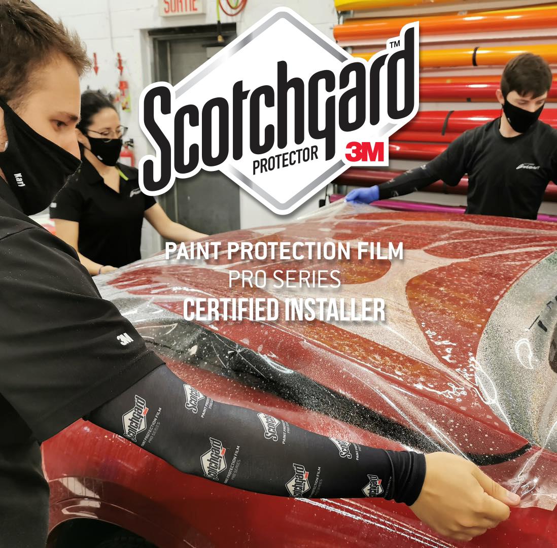 installateurs de pellicule de protection de peinture en action sur un véhicule de luxe